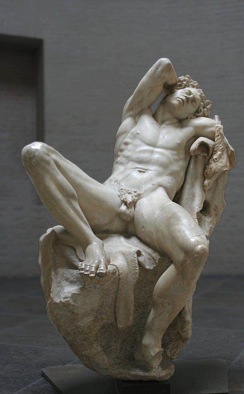 """Fauno Barberini, Copia en mármol de Pérgamo de un bronce helenístico. 220 BCE. 215 cm. Glyptothek, Munich. Vista frontal. """"Sueños sensuales agitan al durmiente e iluminan su rostro vigoroso, enmarcado por la fluyente cabellera y por la corona de yedra con sus corimbos...Un estremecimiento dionisíaco ha quedado fijado en la imagen del estático soñador"""" (W. Fuchs)."""