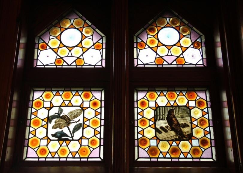 Interior (5). Otro  ejemplo de musicalidad en las vidrieras del baño podemos ver como un gorrión toca el piano y una abeja la guitarra.