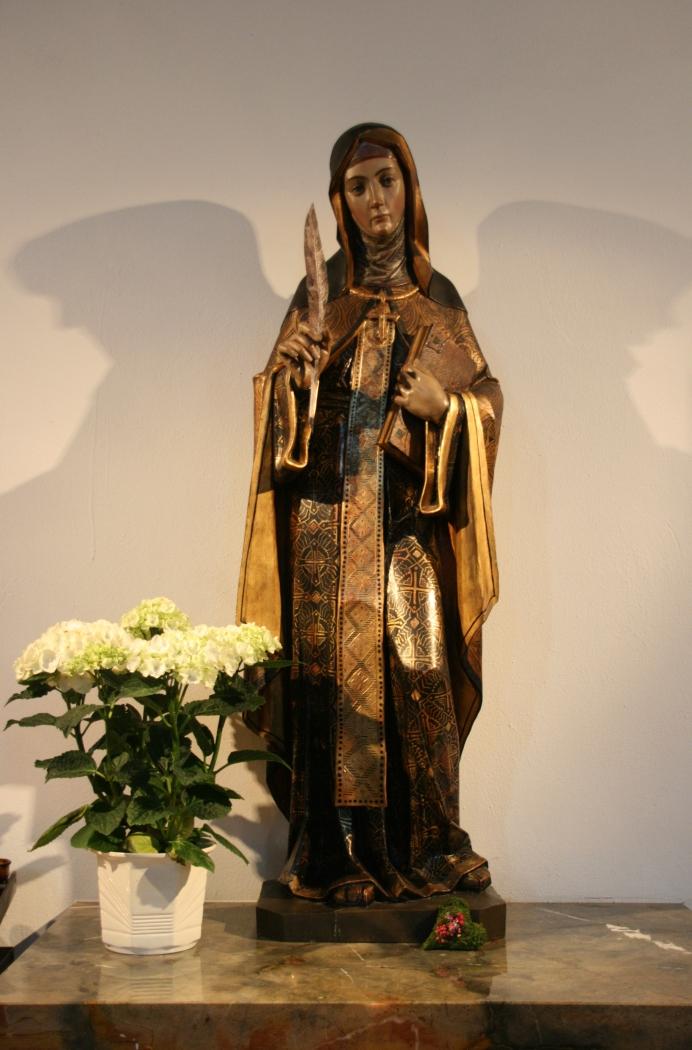 Escultura que representa a Santa Hildegarda, en la iglesia parroquial que lleva su nombre, en Eibingen (Alemania). De artista desconocido, la obra incorpora bellamente los símbolos con que se la identifica: cruz pectoral, pluma, y libro.